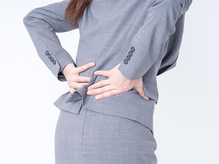 腰を痛がる女性